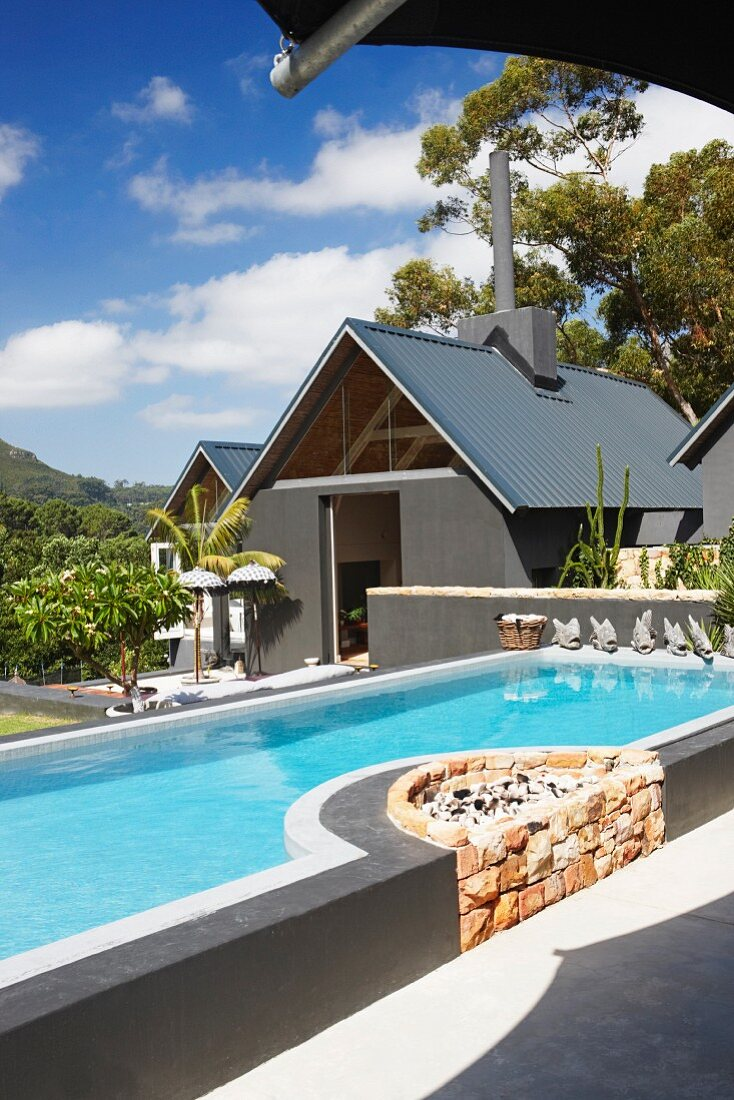 Contemporary pool with integrated, stone fireplace in front of house in tropical surroundings