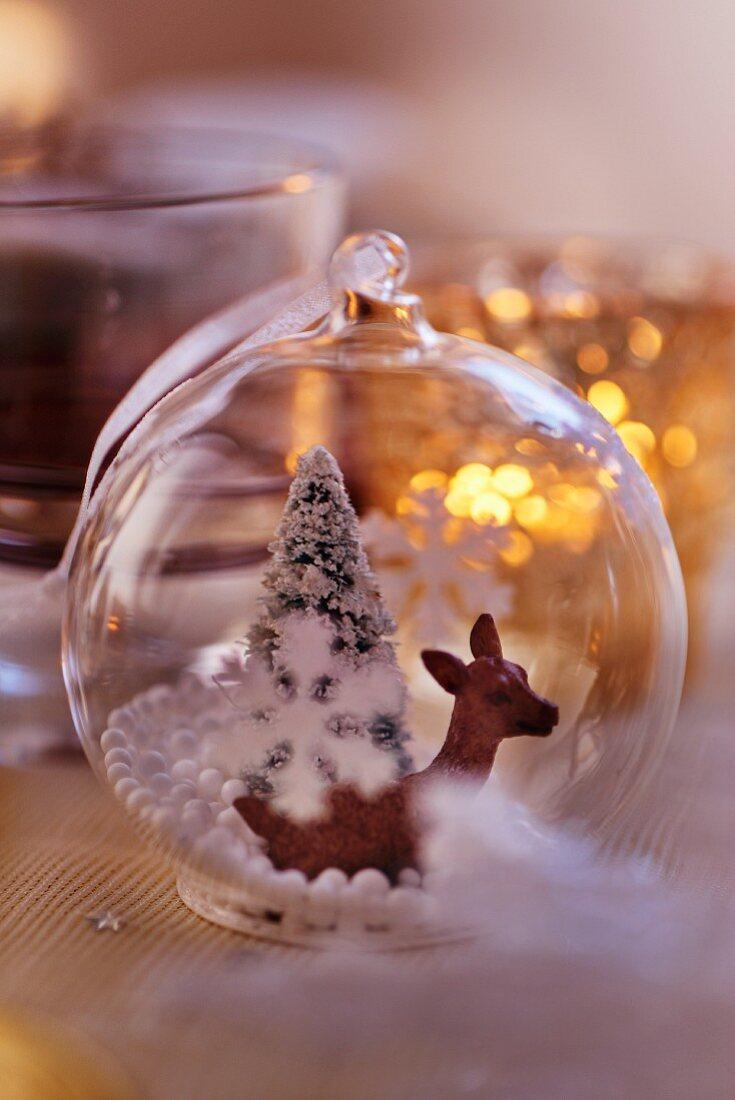 Durchsichtige Christbaumkugel mit Rehfigur und Tannenbaum als Tischdeko für Weihnachten (Close Up)