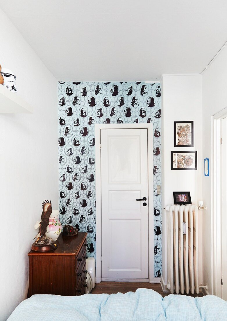 View across bed to white interior door and wall with patterned wallpaper in narrow room