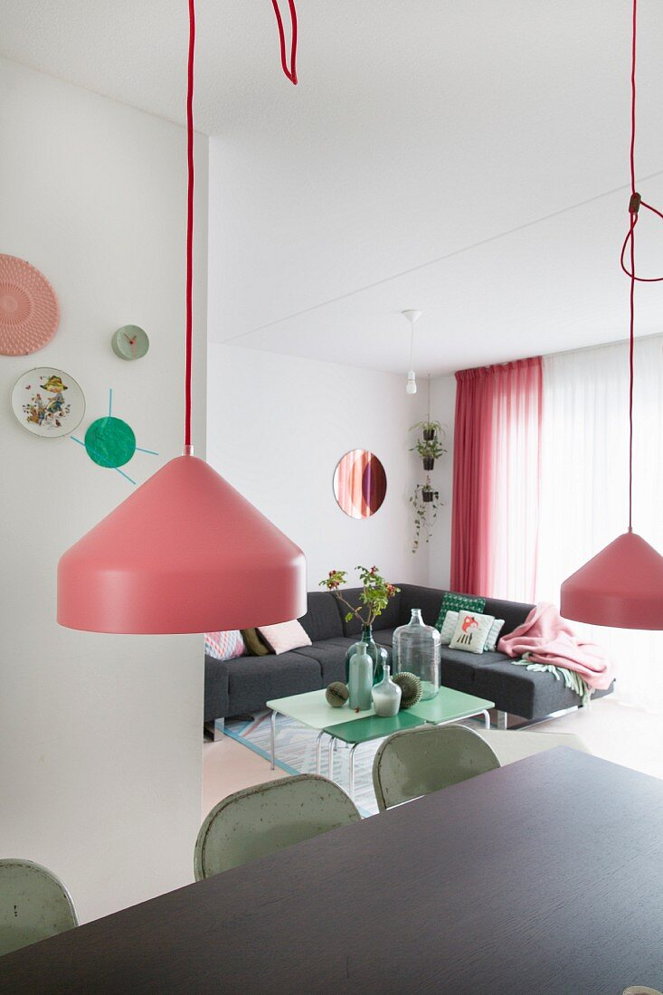Pendant lamps with pink lampshades above dark dining table; grey corner sofa and retro coffee table in background