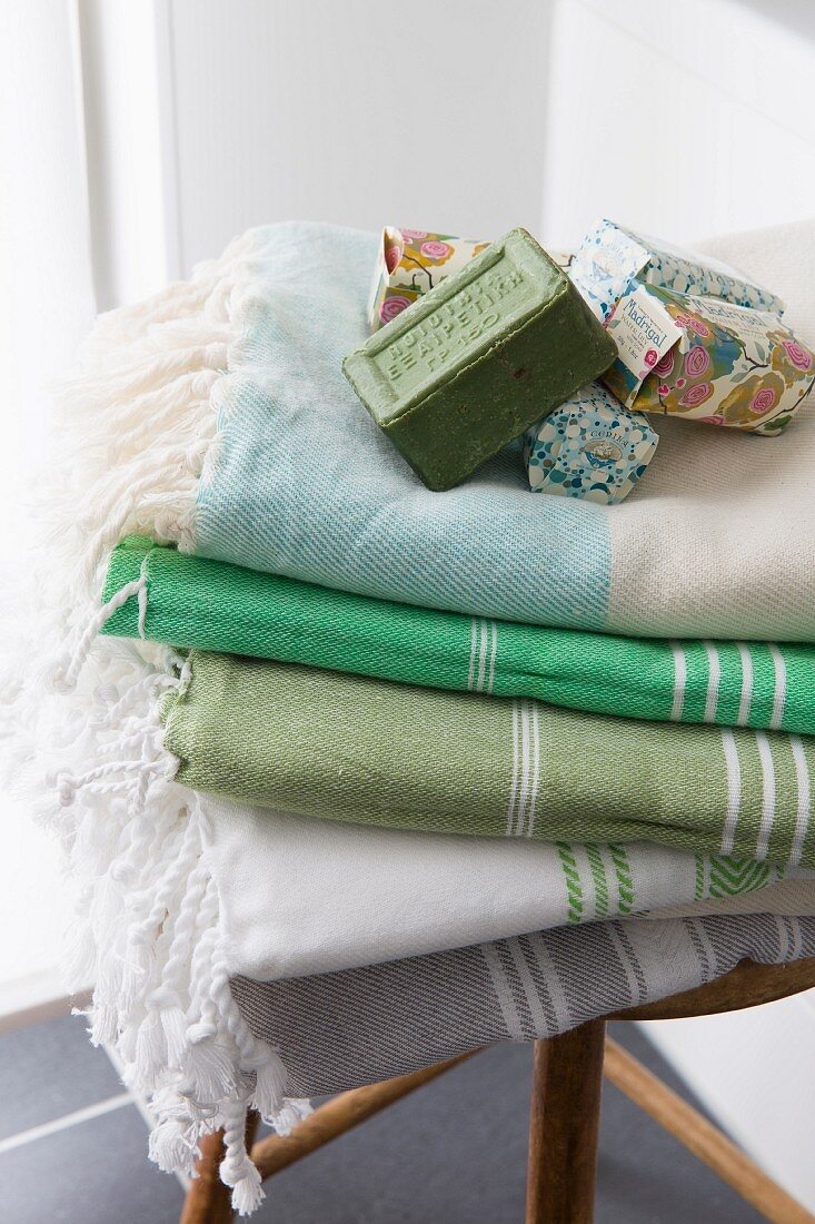 Various soaps and folded towels with fringed edges