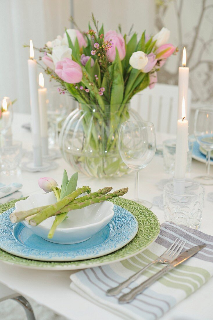 Pastel place setting with asparagus spears and glass vase of tulips on festively set table