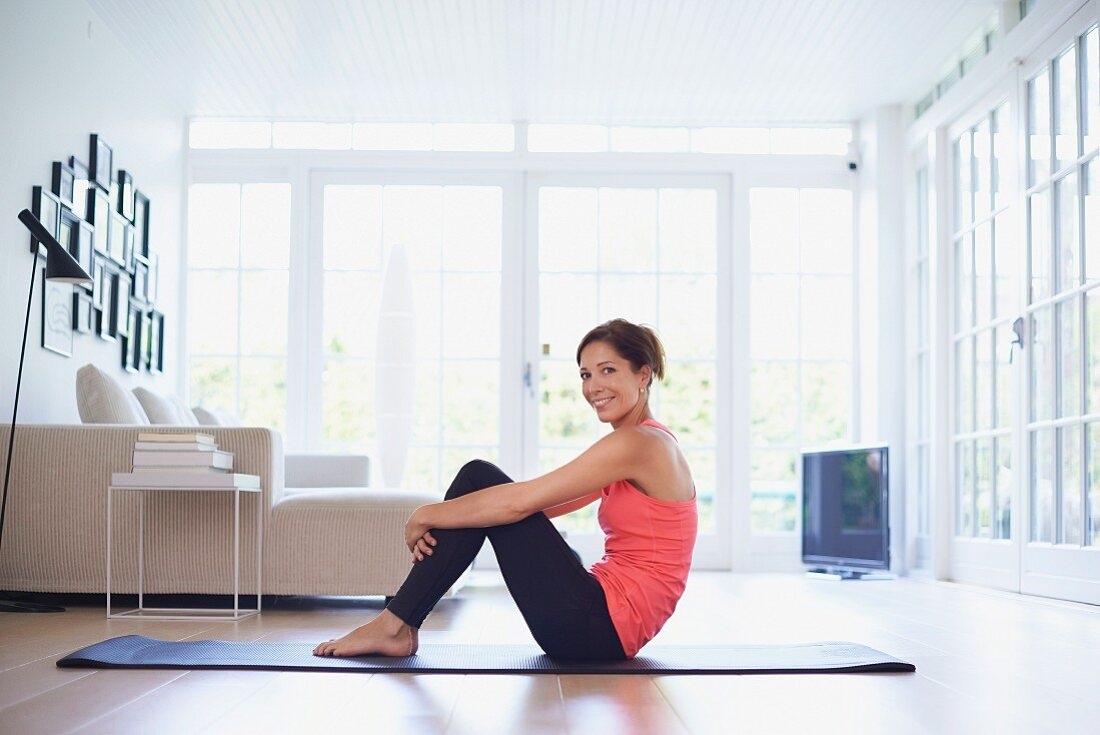 Woman exercising on yoga mat in living room