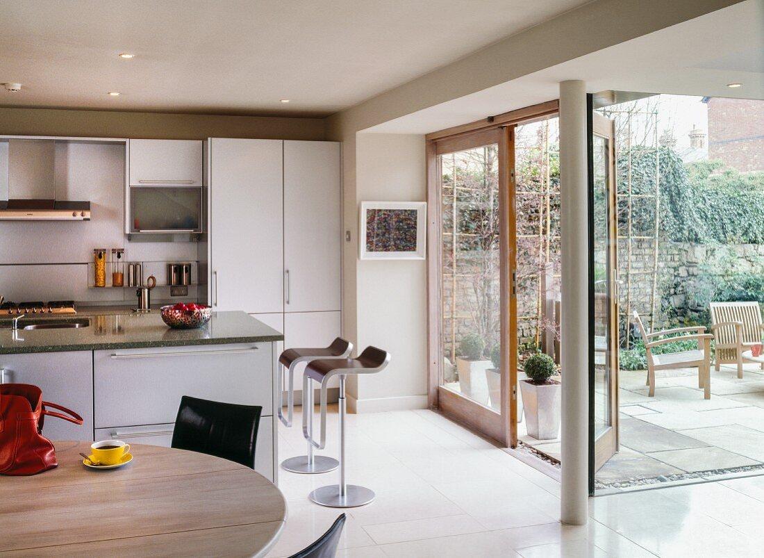 Küche mit Fronten aus gebürstetem Aluminium und Barhocker Lem von Shin und Tomoko Azumi an Kücheninsel; Fensterfront zur Terrasse; vorne runder Esstisch