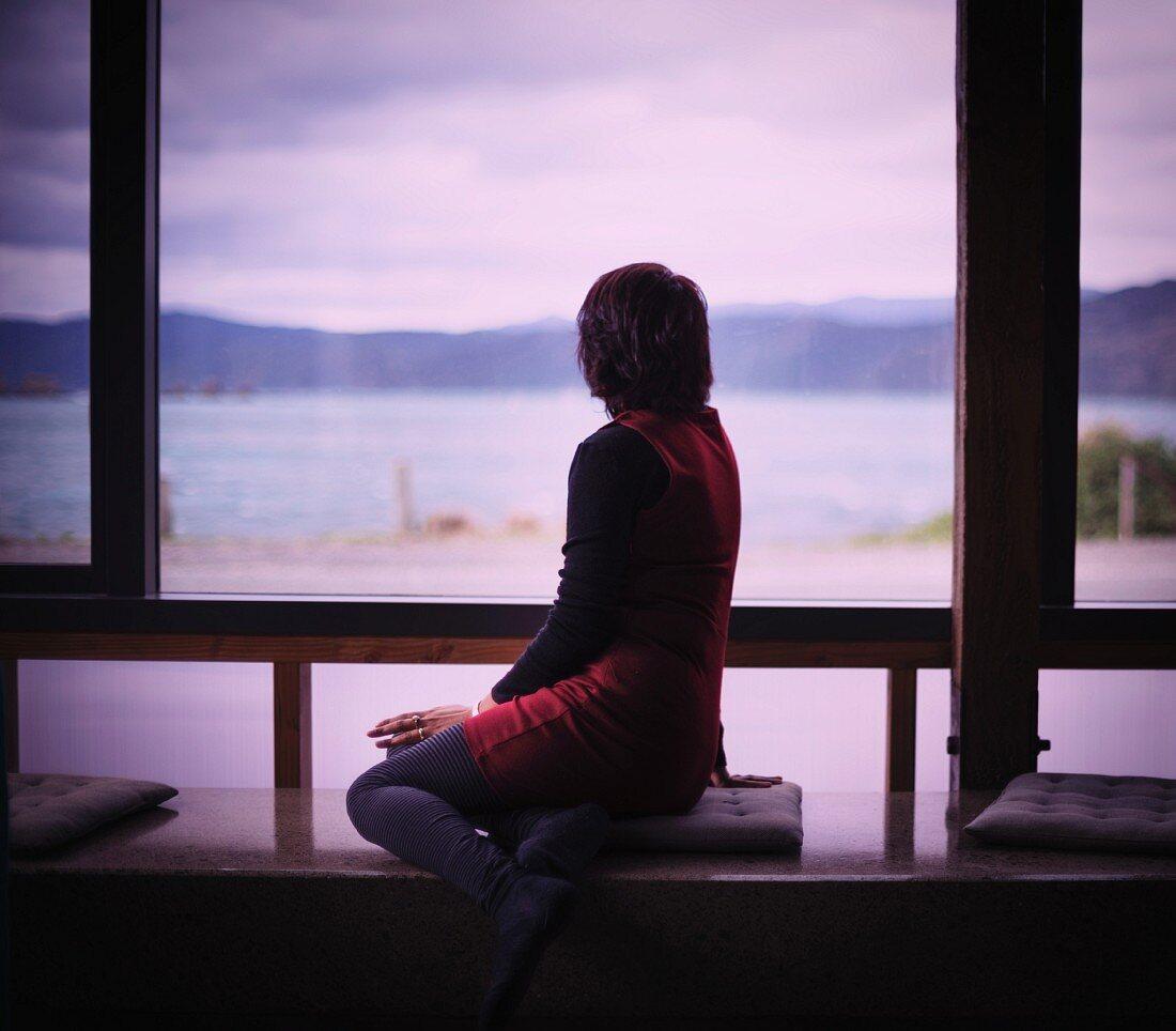 Woman sitting on window seat next to glass wall