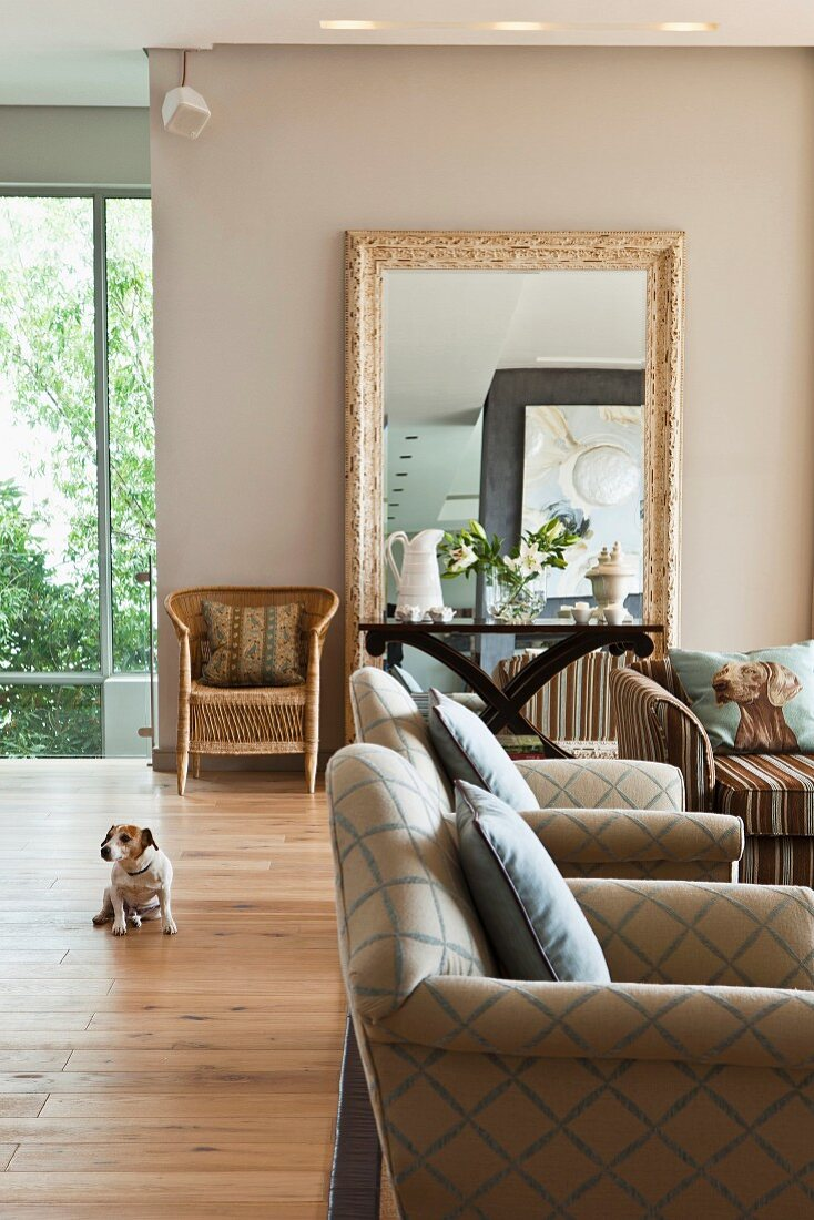 Living room with diamond-patterned armchairs, side table and large, framed mirror against beige wall in background