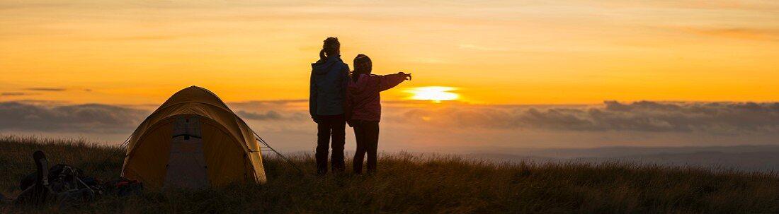 Silhouette von zwei Wanderern mit Blick auf den Sonnenuntergang