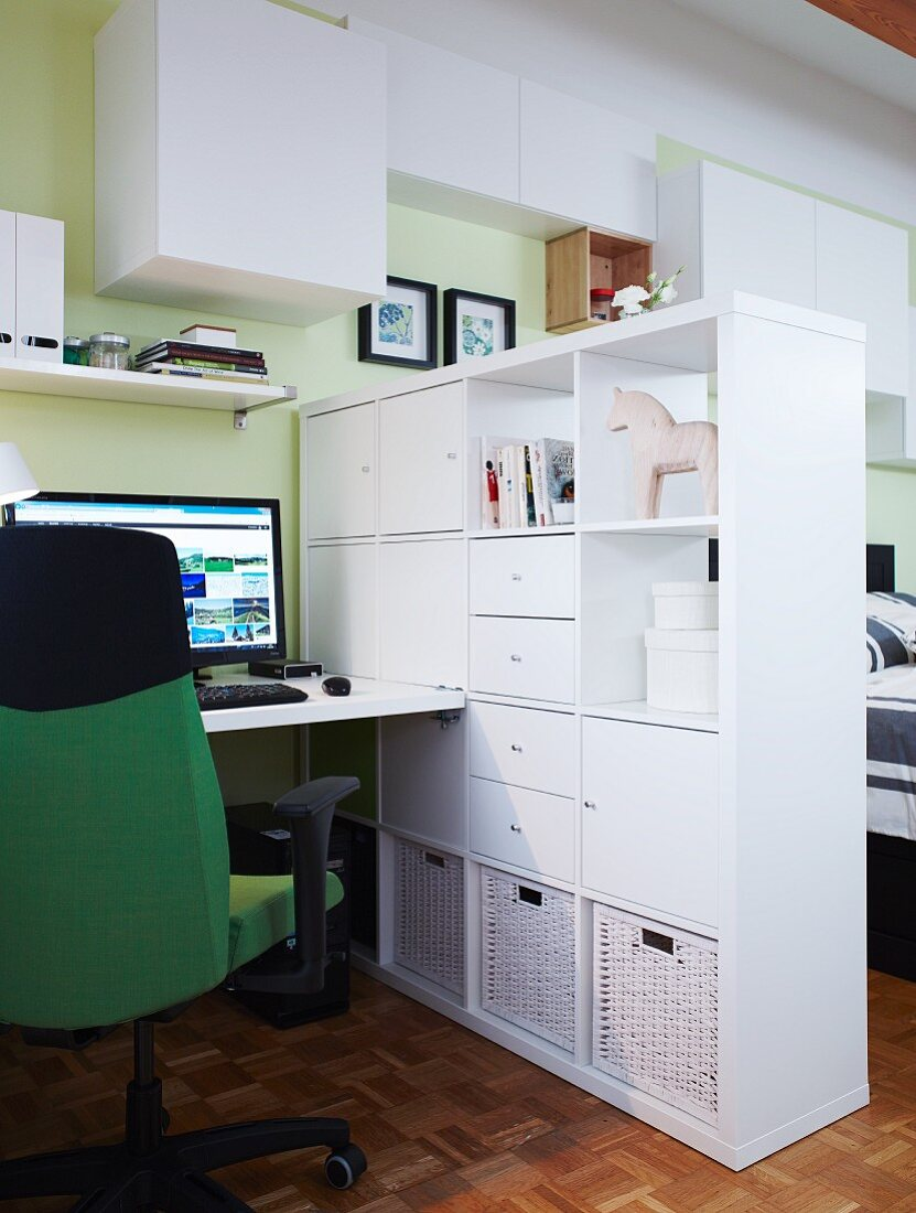 Lots of space on a simple, white room divider between a bed and a home office
