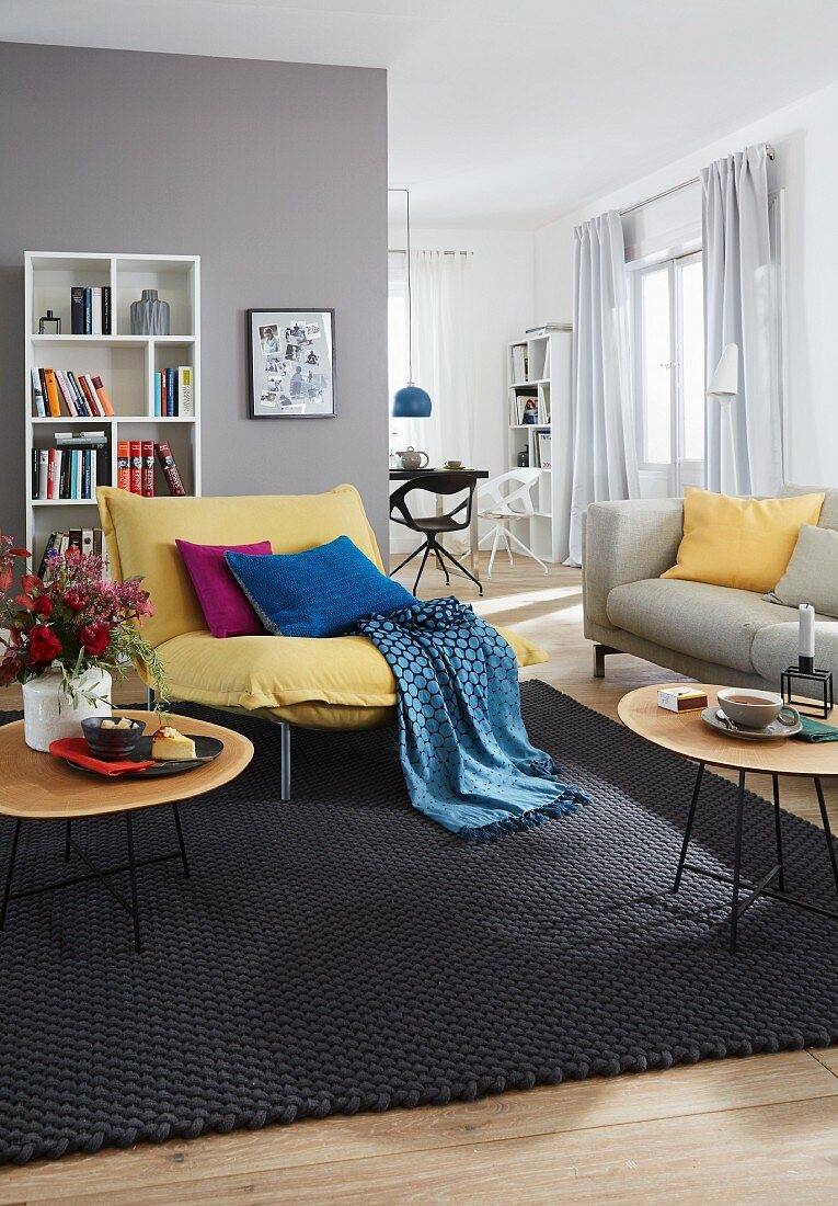 A grey living room with a yellow armchair with a throw and cushions and a white bookshelf