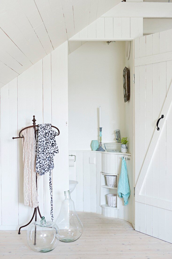 Wrought iron, antique-style valet stand and glass demijohns against white wooden wall of guest toilet under sloping attic ceiling