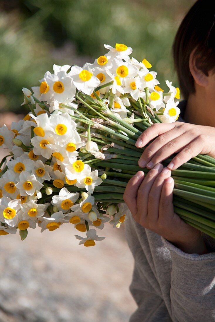 Boy holding bouquet of narcissus in garden