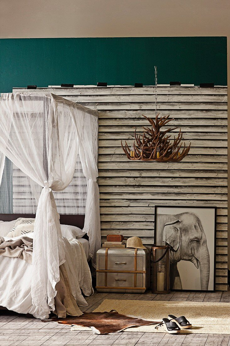 African-style bedroom - four-poster bed with fabric canopy next to metal bedside table, drawing of elephant against board wall and antler chandelier hung from ceiling