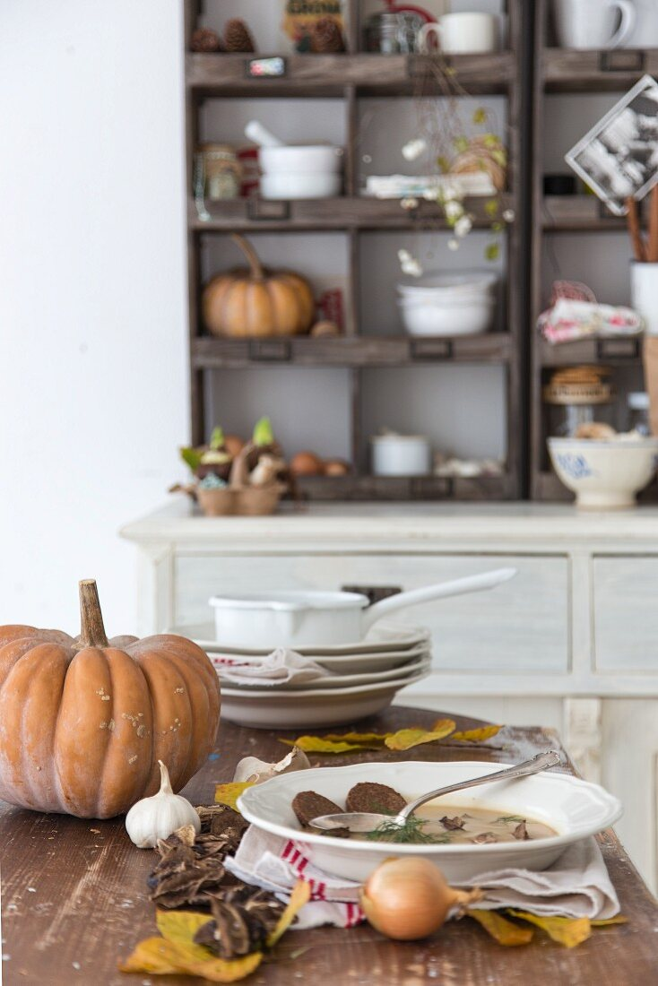 Soup plates and autumn arrangement of leaves and vegetables on kitchen table in rustic interior
