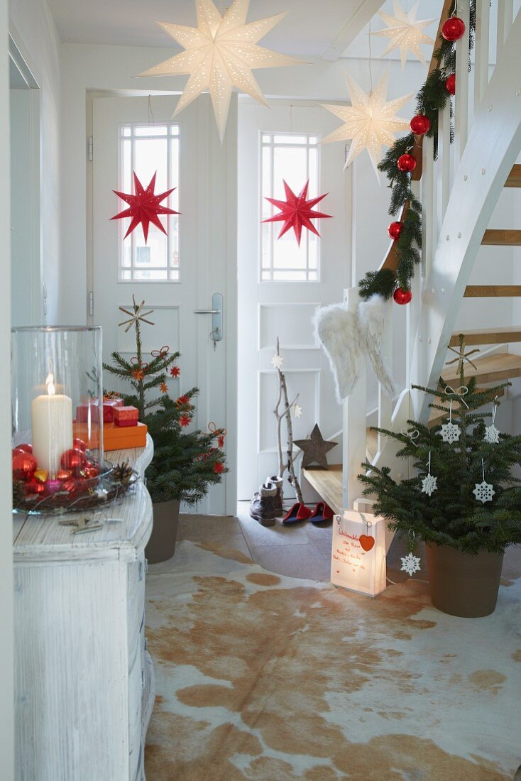 A hallway decorated for Christmas with decorated trees and garlands on the banister