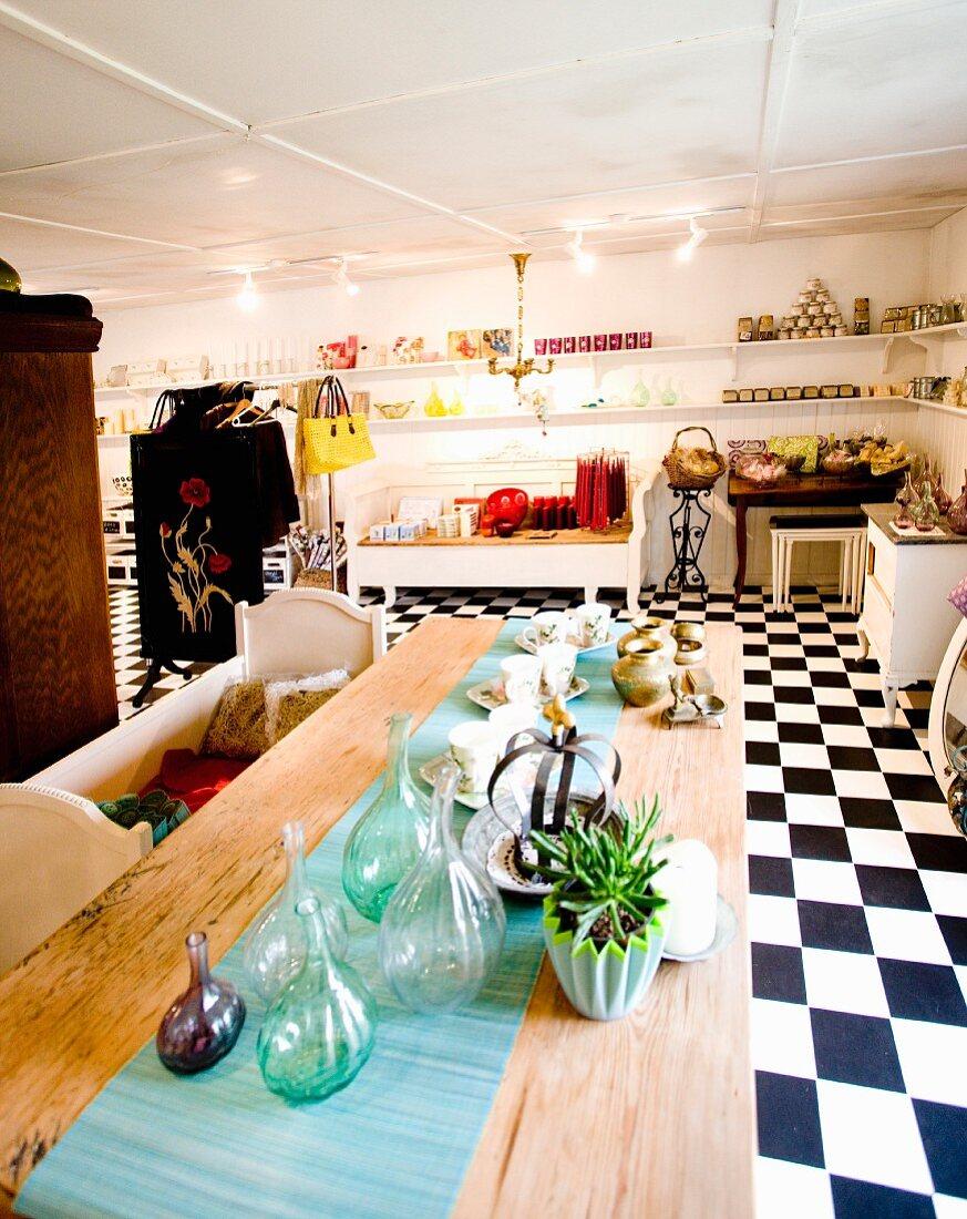 Showroom mit Schachbrettmusterboden, auf langer Holztafel Flaschensammlung, Geschirr und türkiser Läufer