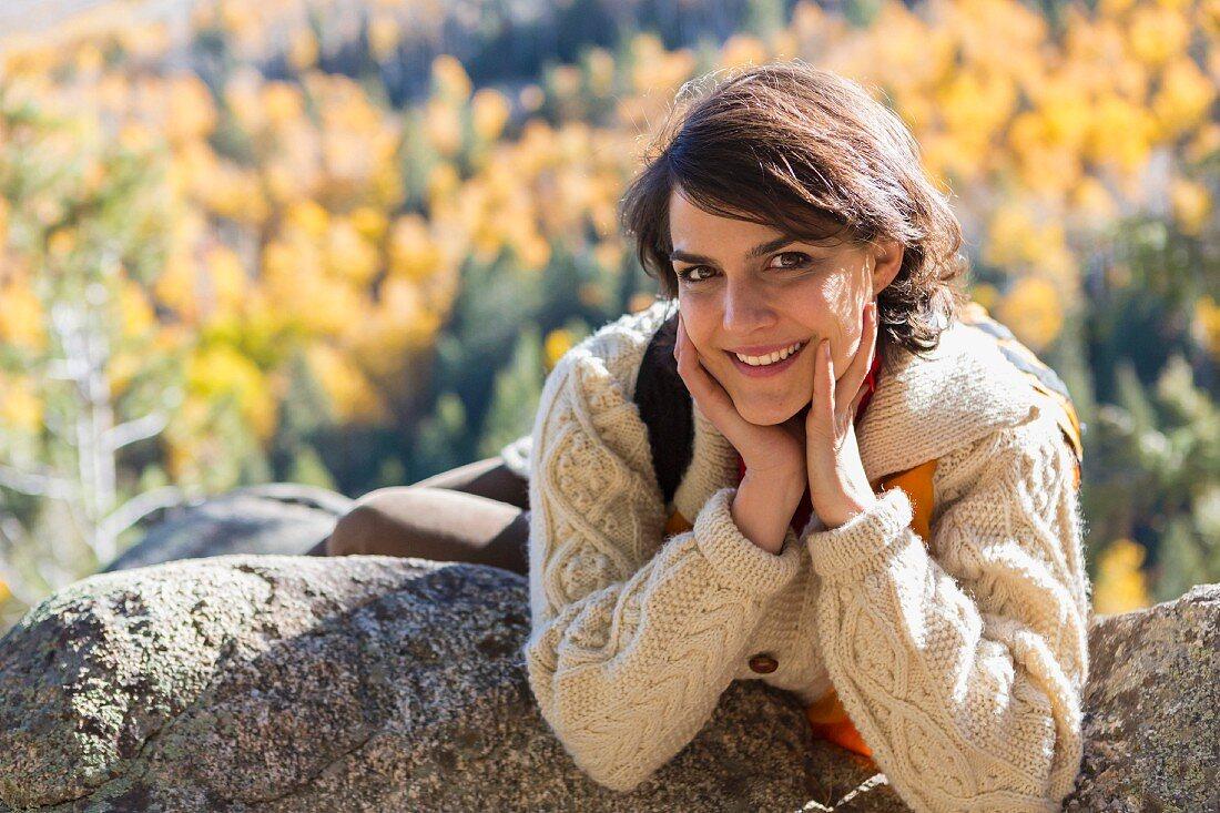 Woman wearing hiking gear lying on rock ledge in autumnal mountain landscape