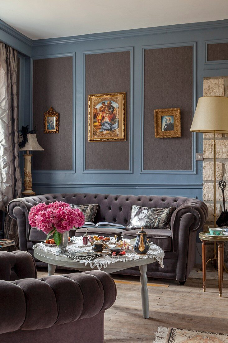 Button-tufted sofa below gilt-framed pictures on elegant wood panelling painted grey and blue