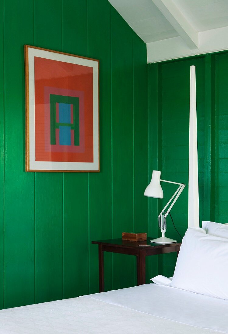 Abstract picture on wooden wall painted green next to bed with bedposts and snow-white bed linen