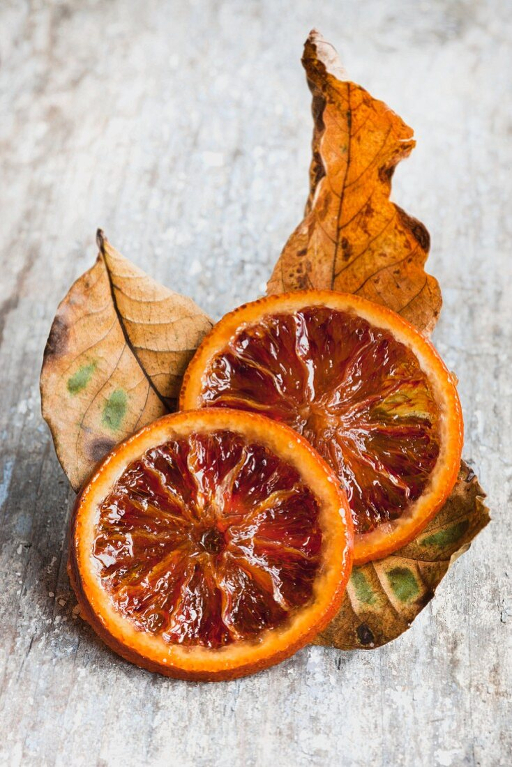 Two slices of caramelised blood-orange slices and dried leaved on wooden surface