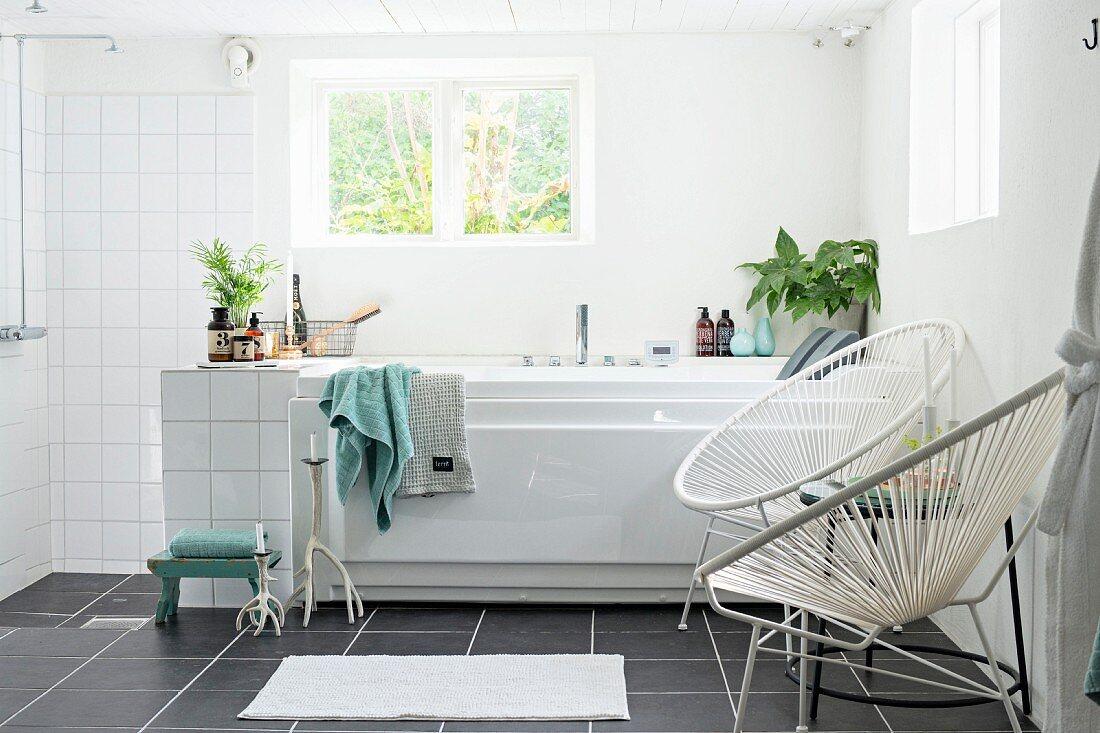 Retro Sessel mit weisser Seilverspannung neben Badewanne am Fenster, offener Duschbereich in modernem, weißem Bad