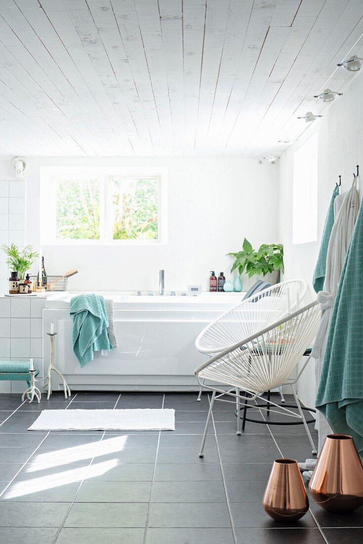 Copper vases on grey-tiled floor, retro cord chairs next to bathtub below window in modern, white bathroom