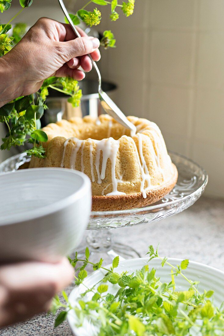 Decorating a bundt cake with white icing