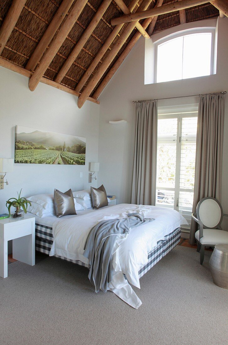 Double bed next to French windows with floor-length curtains in bedroom with exposed bamboo roof structure