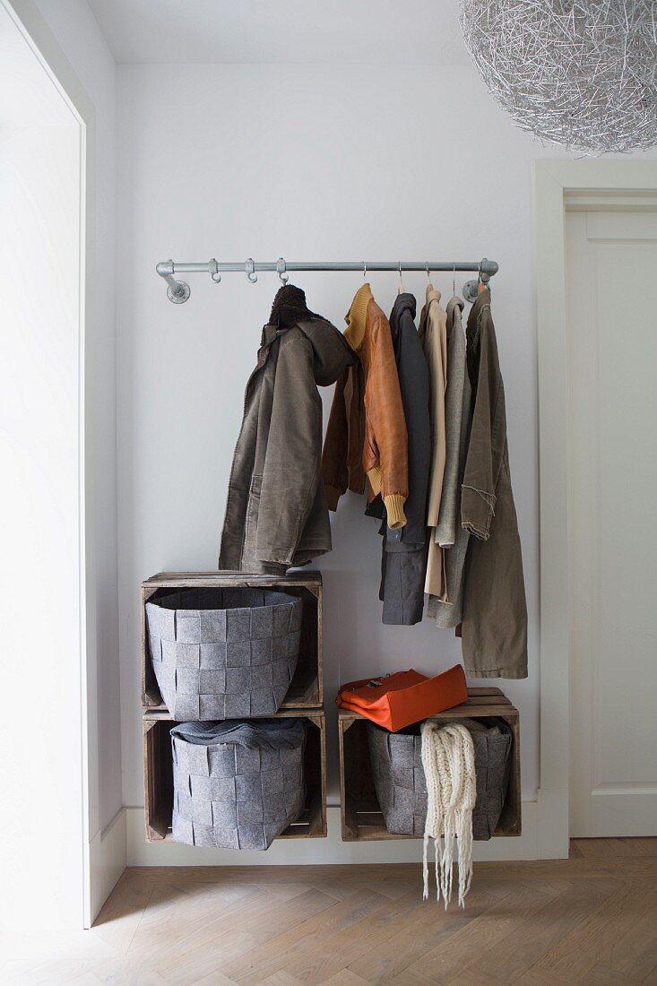 Coats hanging from open coat rack above felt baskets in wooden crates