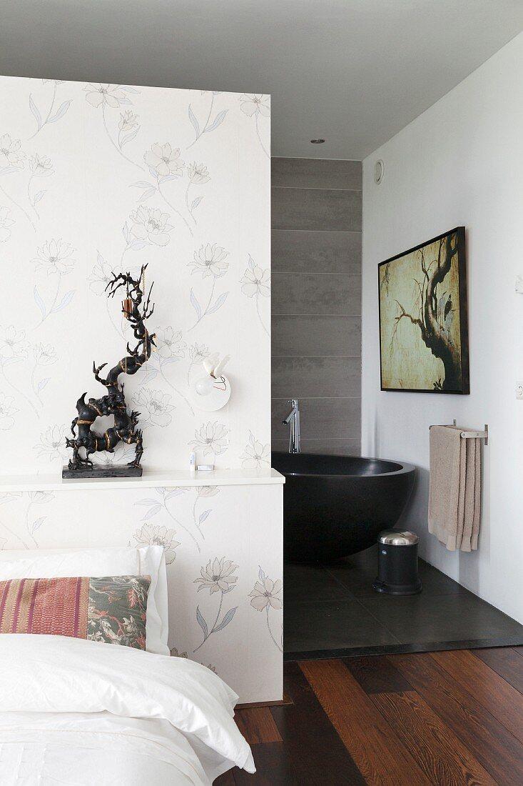 Dezente Blumentapete an Wandscheibe mit Ablagefläge und Ethnokunstobjekt, Blick auf freistehende schwarze Badewanne in Bad Ensuite
