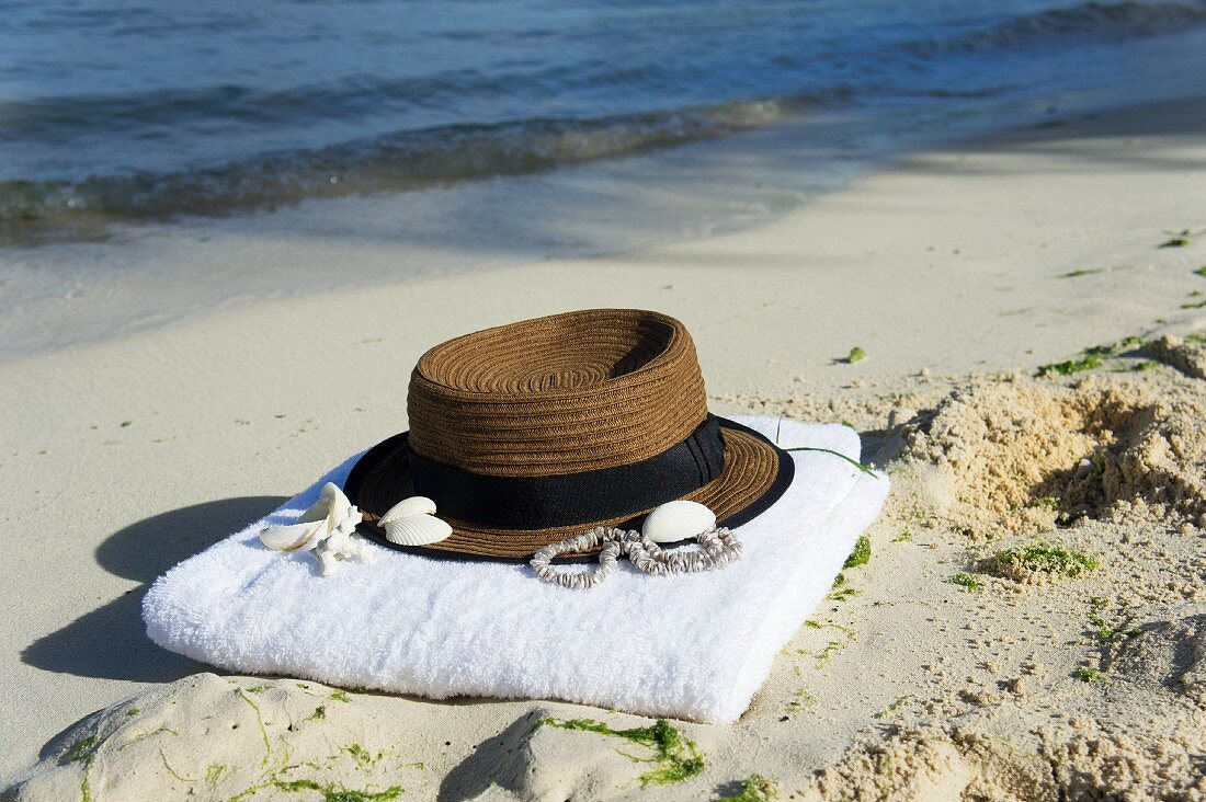 Hat and towel on sandy beach