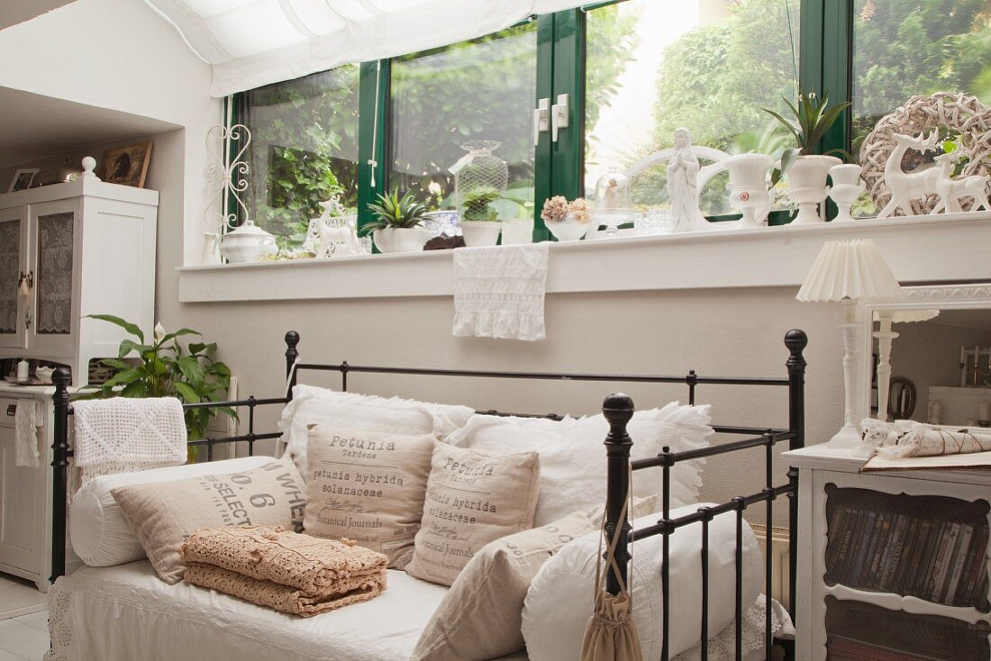 Couch with vintage metal frame and cushions below strip of windows with green-painted frames