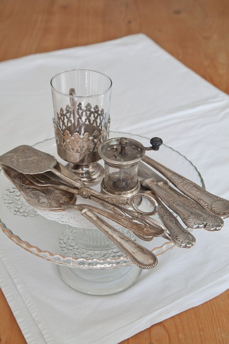 Vintage silver cutlery on cake stand and white place mat