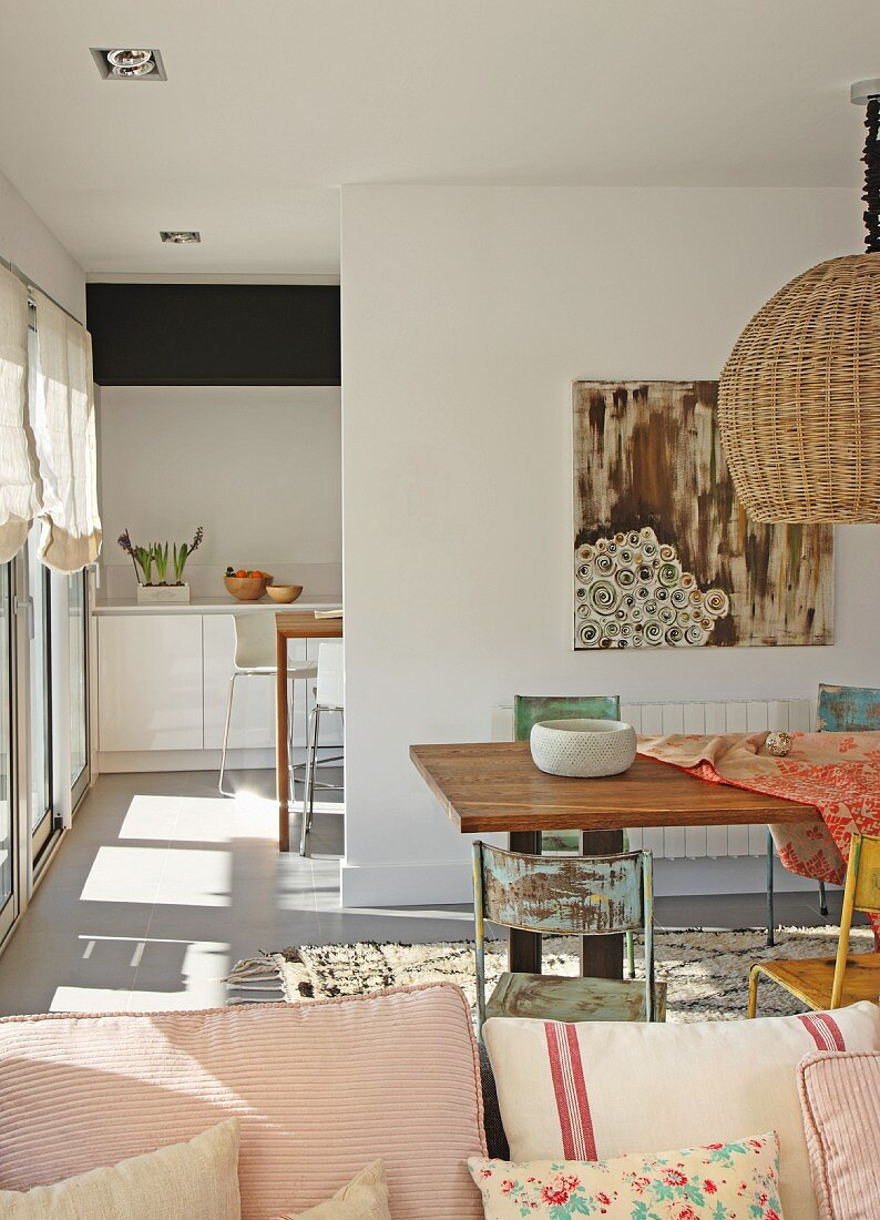 View past cushions to dining area with vintage metal chairs and floor-to-ceiling doorway leading to kitchen