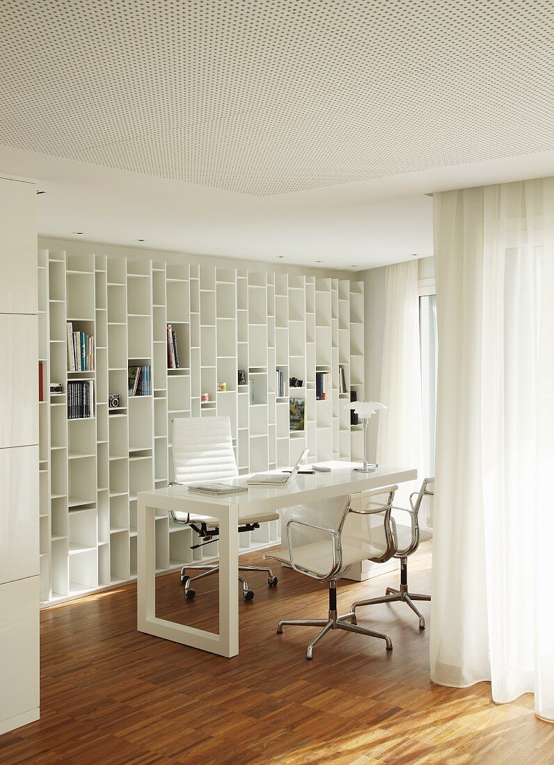 Workspace with Eames Aluminium Chairs and fitted shelving integrated into white interior