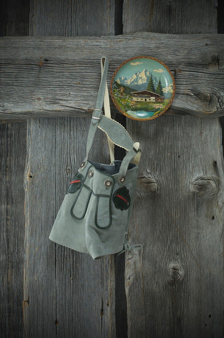 Lederhosen and painted wooden plate hanging on weathered wooden wall