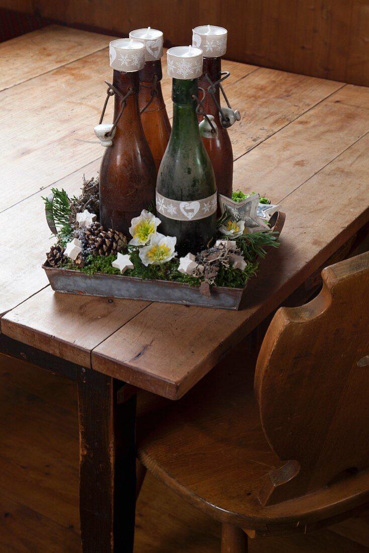 Rustikaler Adventskranz aus vier alten Bügelflaschen mit Teelichtern darauf in einem Metalltablett