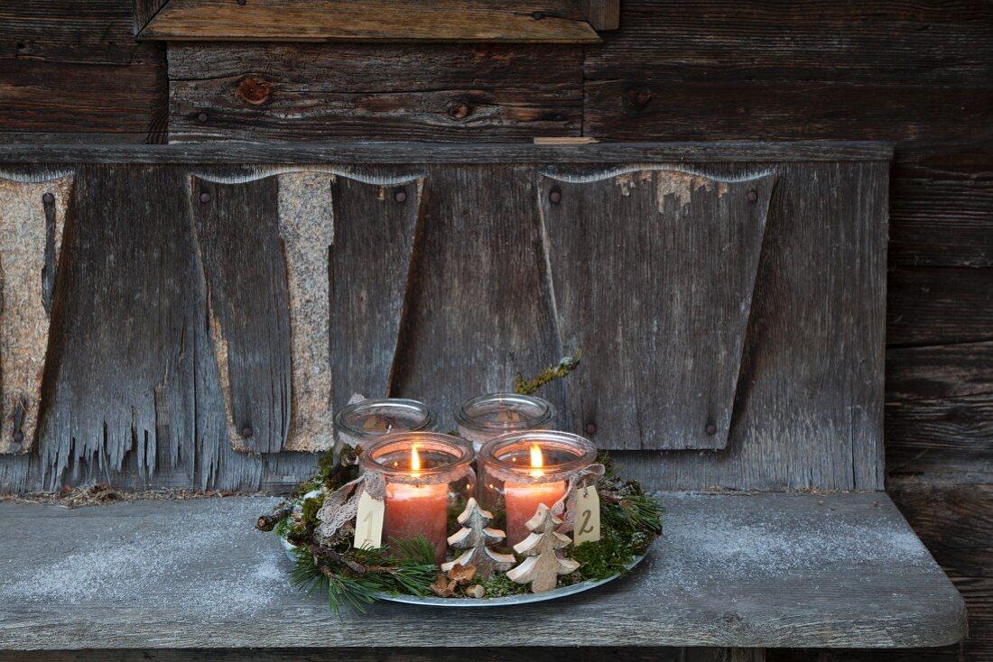 Rustikaler Adventskranz mit zwei brennenden Kerzen in Weckgläsern auf einer verwitterten Holzbank