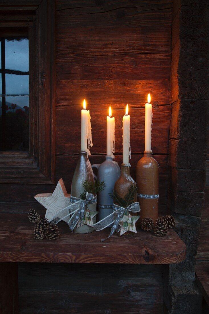 Rustikaler Adventskranz mit vier brennenden Kerzen in verschiedenen Flaschen aus Steingut