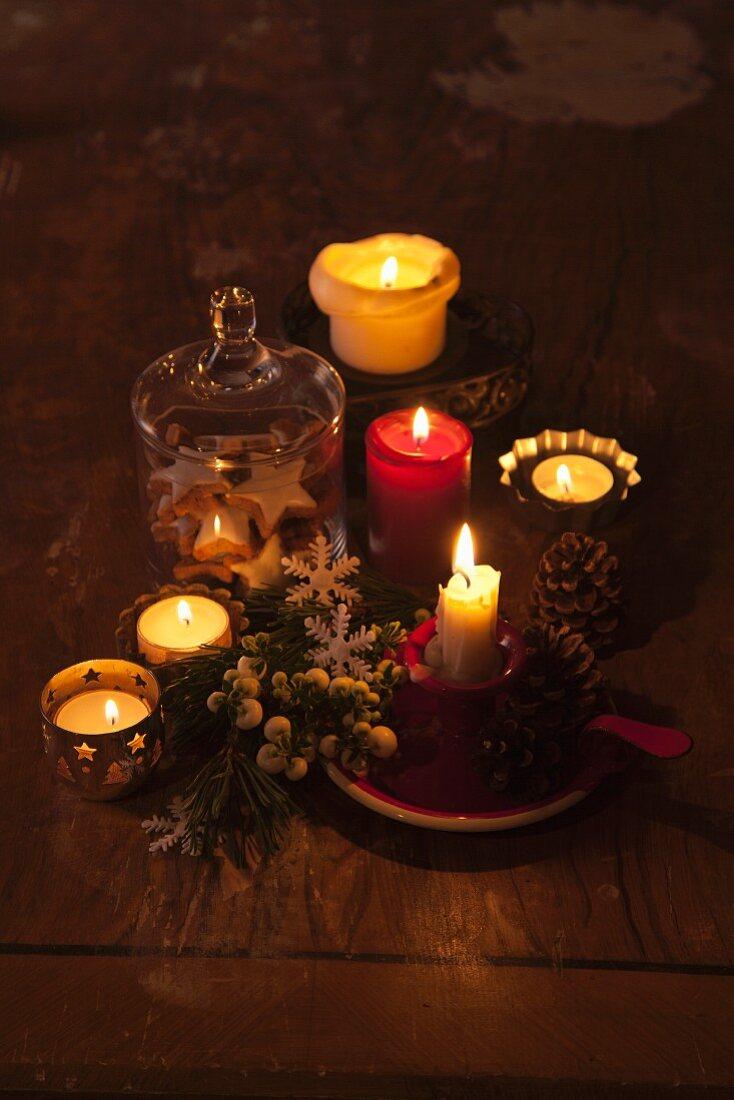 Schummriges Licht von brennenden Kerzen und Teelichtern mit weihnachtlicher Deko