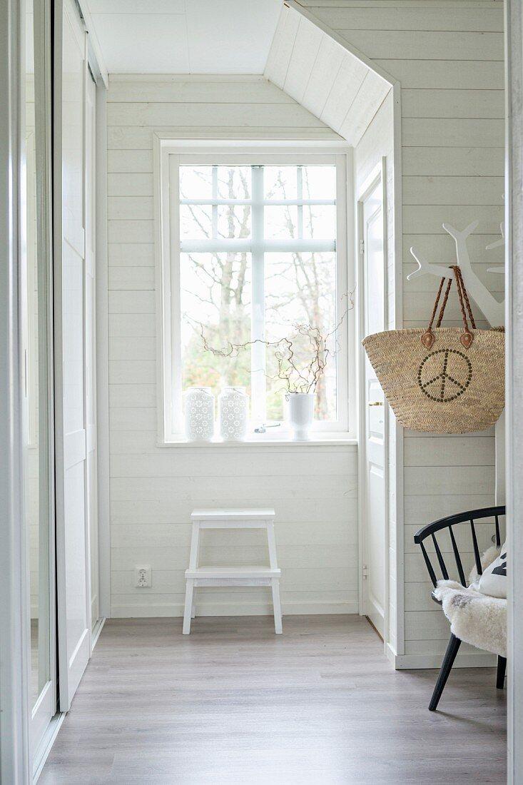 White, wood-panelled hallway with step ladder below window
