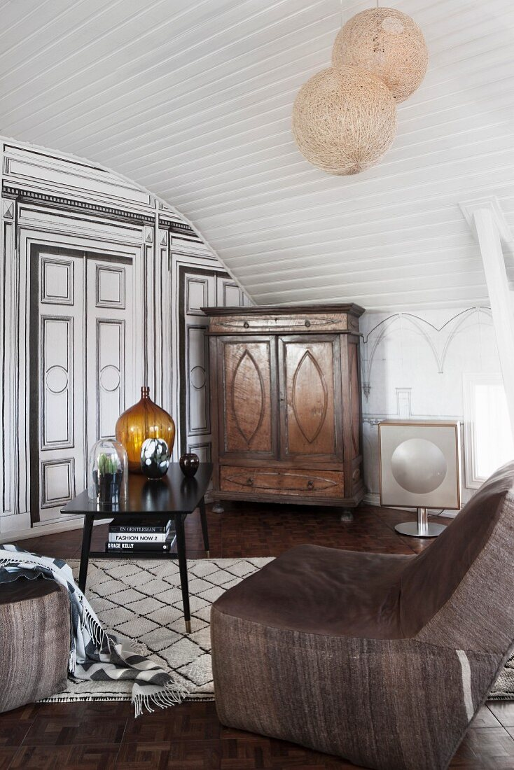 Lounge area with easy chair and black table in attic room with white, wood-panelled arched ceiling