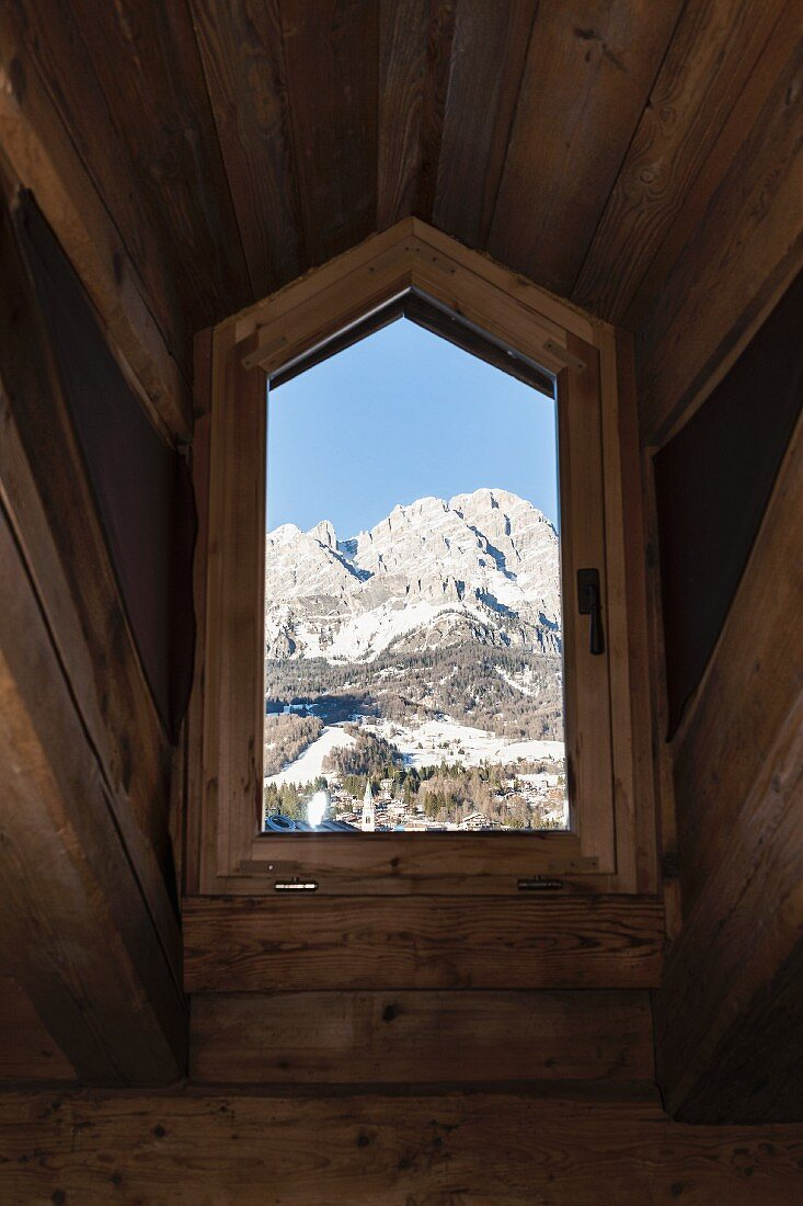 Blick auf die Dolomiten durch rustikales Dachgaubenfenster eines Chalets