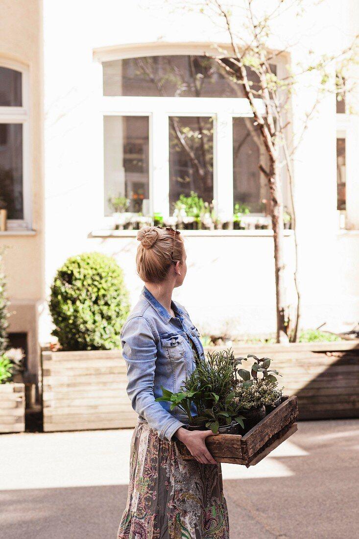 Woman carrying wooden crate of garden herbs