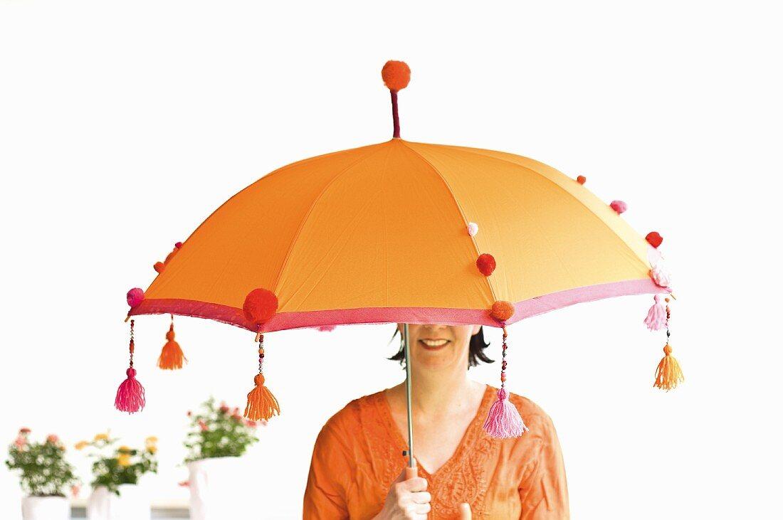 Woman under orange Balinese parasol