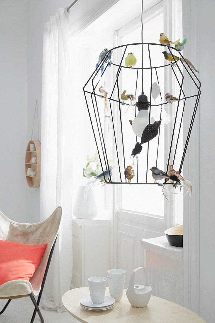 A wire-framed pendent lamp decorated as a birdcage with colourful glass birds