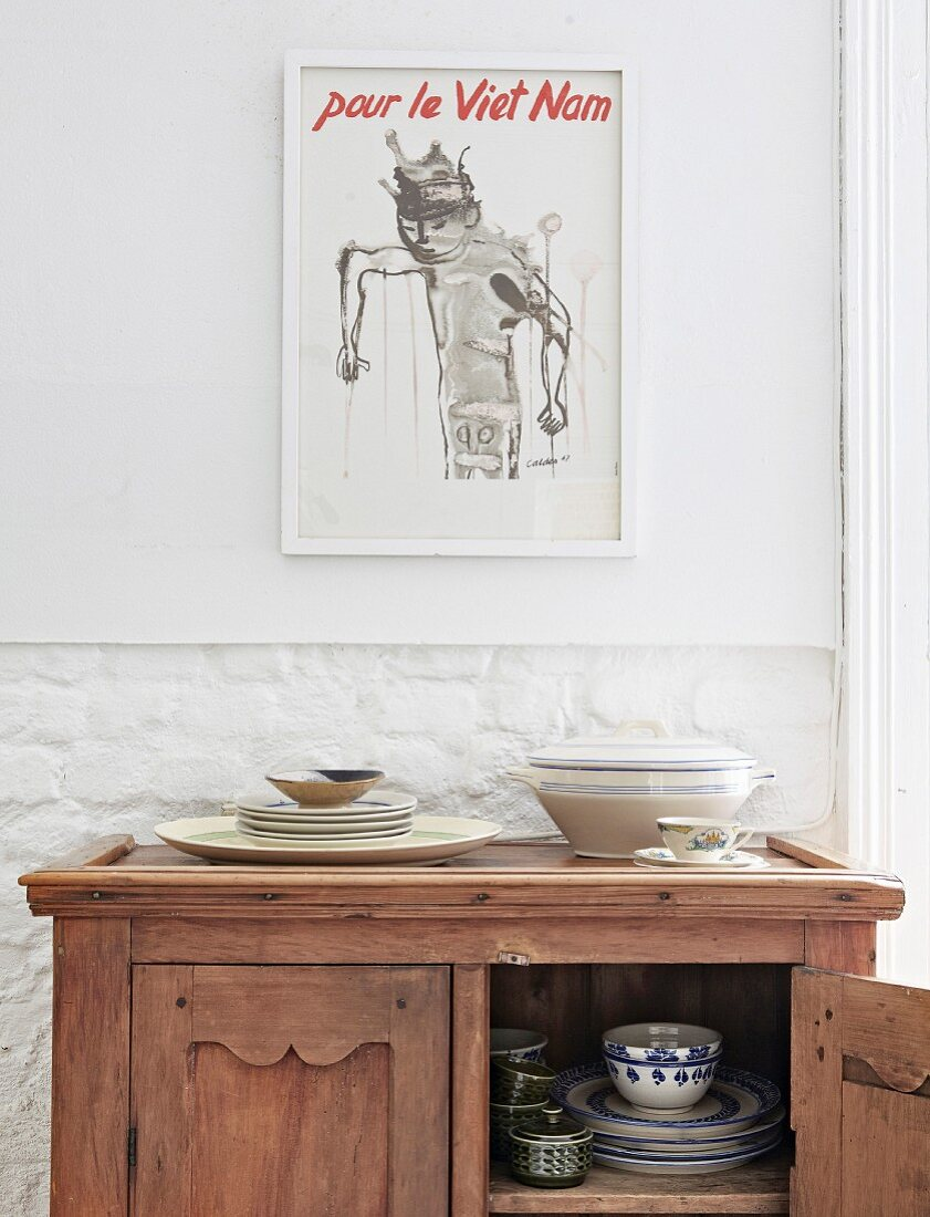 Crockery in antique half-height cabinet below modern printed poster
