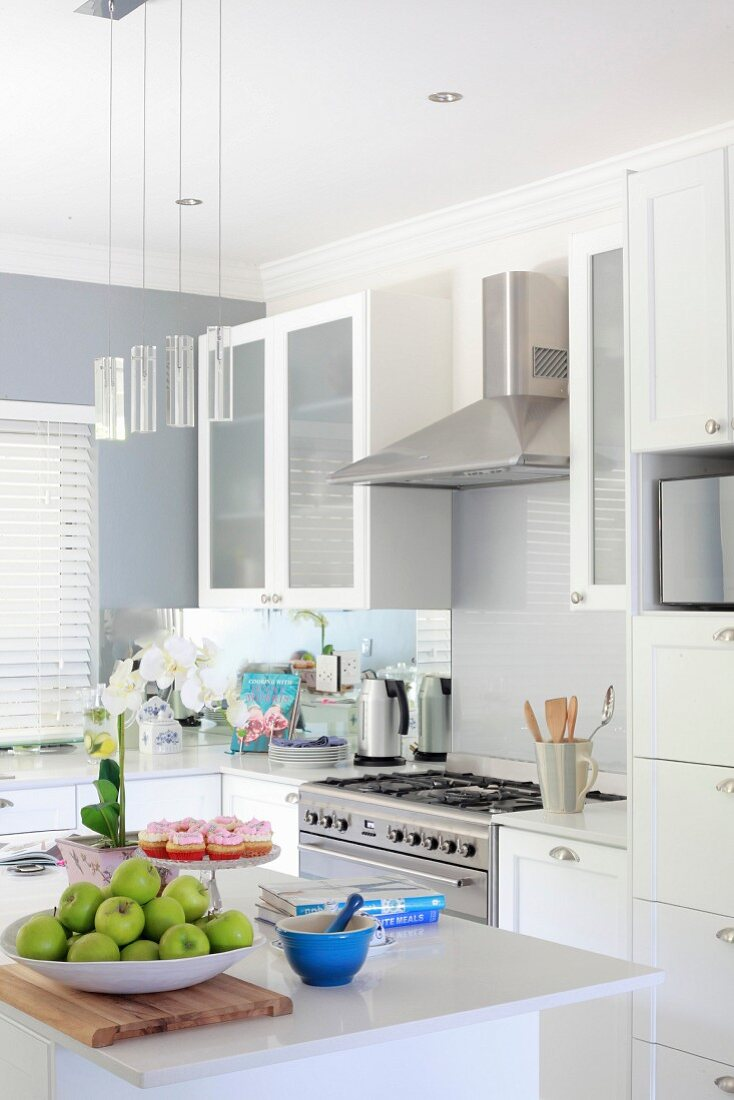 Bowl of apples on island counter in modern fitted kitchen with white fronts