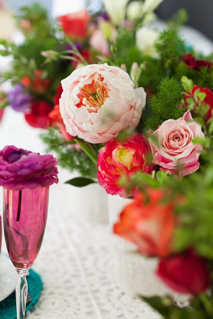 Arrangements of colourful summer flowers decorating table