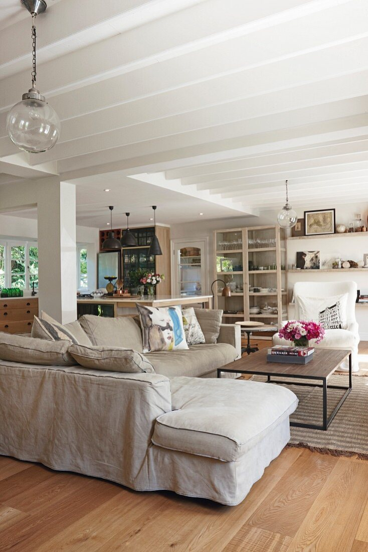 Open-plan country-house-style living area with comfortable beige couch and white wood-beamed ceiling