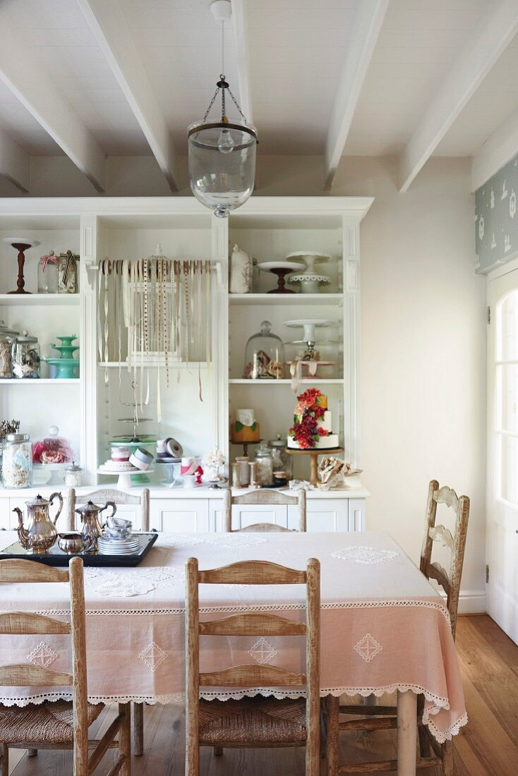 Country-house interior with various cake stands and ribbons on white shelving